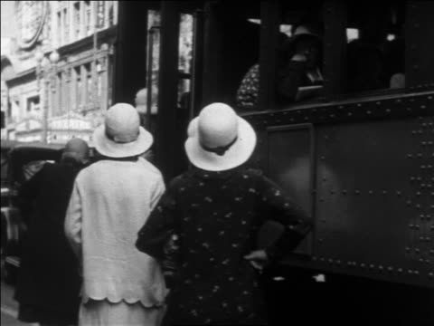 b/w 1930 rear view people boarding trolley on city street / los angeles, ca - tram stock-videos und b-roll-filmmaterial