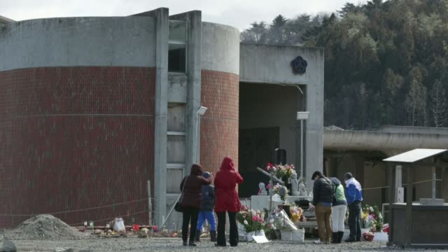 vidéos et rushes de people bow in front of a memorial with the list of the dead on the third anniversary of the great east japan earthquake and tsunami at the okawa... - composition florale