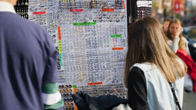 people browse display of piercing stall, camden high street - belly button piercing stock videos & royalty-free footage