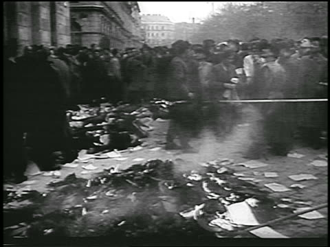 vídeos de stock e filmes b-roll de people burning piles of soviet books in street during hungarian revolution / newsreel - 1956