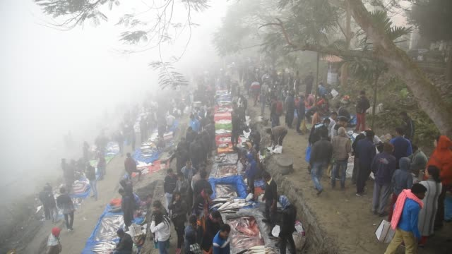 People buy fish at a fish market in the banks of Brahmaputra on the occasion of Uruka in the eve of Bhogali Bihu the annual festival of feast at Uzan...