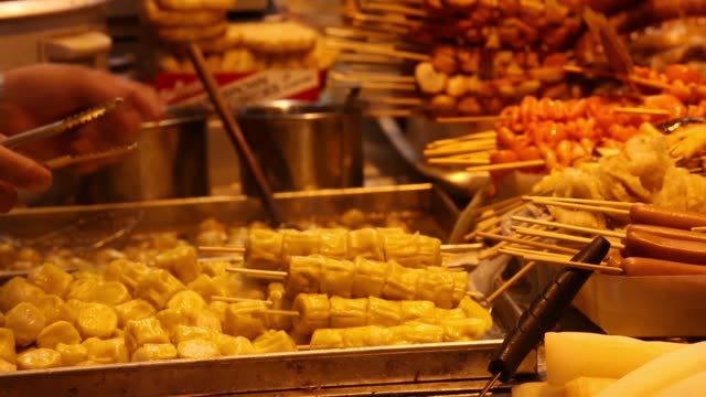 vidéos et rushes de people buy food from a street side food stall or dai pai dong in the mong kok district of hong kong market workers prepare food at street stall... - mong kok
