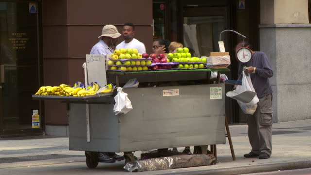 People buy fruit from a mobile food vendor in New York City.