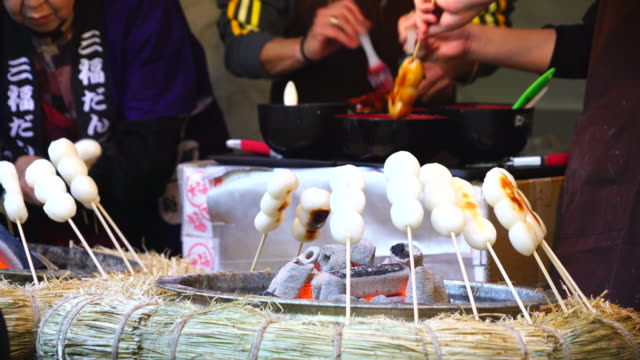people buy mitsufuku dango (steamed rice flour dumpling of the charcoal fire grill) at momiji cyaya (tea house) in rikugien garden (traditional japanese garden) bunkyo-ku tokyo on december 03 2017. - スイーツ点の映像素材/bロール