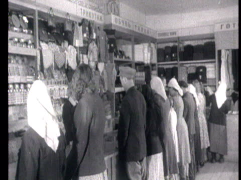 people buying clothes and fabric dishes samovars and even horses harness at local department store and other domestic goods at smaller shop / russia... - 1939 stock-videos und b-roll-filmmaterial