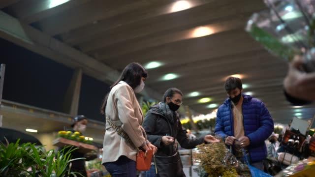 menschen kaufen blumen auf nachtmarkt - mit gesichtsmaske - straßenmarkt stock-videos und b-roll-filmmaterial