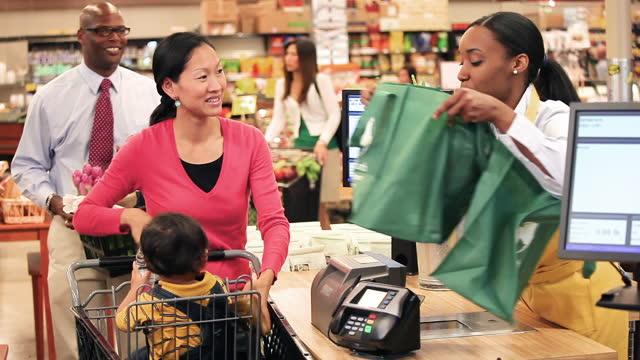 vídeos y material grabado en eventos de stock de people buying groceries at cash register - pagar