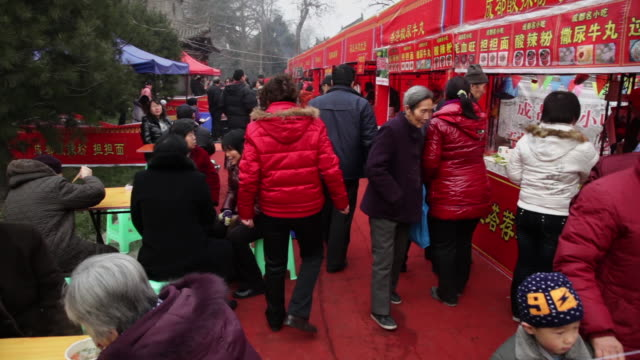 ms pan people buying snacks at temple fair to celebrate chinese spring festival / xi'an, shaanxi, china - gemeinsam gehen stock-videos und b-roll-filmmaterial