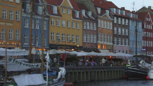 zo, ws, people by canal with colorful houses in background at dusk, nyhavn, copenhagen, denmark - mellanstor grupp av människor bildbanksvideor och videomaterial från bakom kulisserna