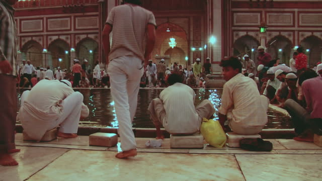 WS TD People by pond in courtyard of Jama Masjid in holy month of Ramzan / Delhi, India