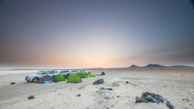 t/l の人々は日の出のビーチでキャンプ - テント点の映像素材/bロール