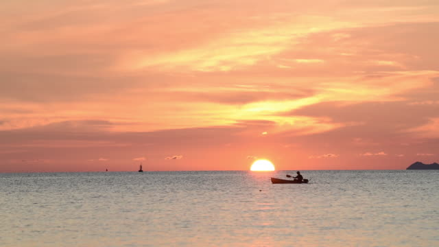 people canoeing pass big sunset at beautiful tropical beach in thailand - omega sun mirage stock videos & royalty-free footage