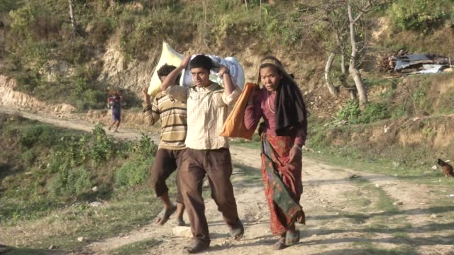 People carry bags of food back to small villages after receiving them from a distribution center / A major earthquake hit Kathmandu midday on...