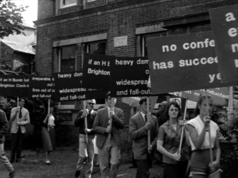 people carry placards during an anti nuclear protest in brighton. 1960. - nuclear bomb stock videos & royalty-free footage