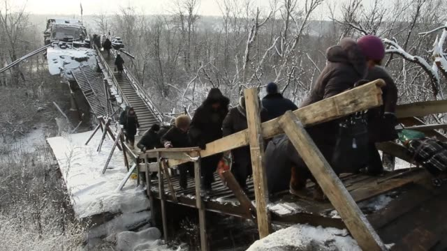 People carry their bags on a wooden ladder placed where the main bridge was destroyed because of fighting as they cross the checkpoint between...