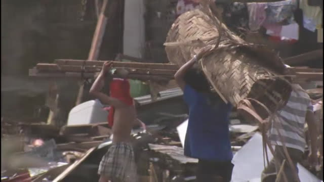 people carry wicker objects down damaged streets in tacloban, philippines after typhoon haiyan causes mass destruction in 2013. - rebuilding stock videos & royalty-free footage