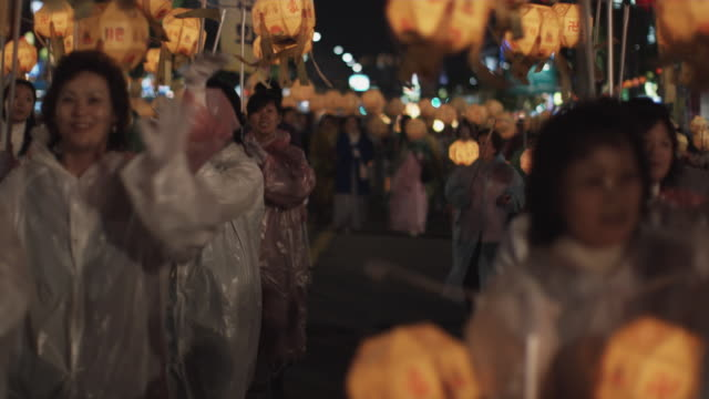 cu selective focus people carrying illuminated paper lanterns at buddha's day lantern parade, night, seoul, south korea - lantern stock videos & royalty-free footage