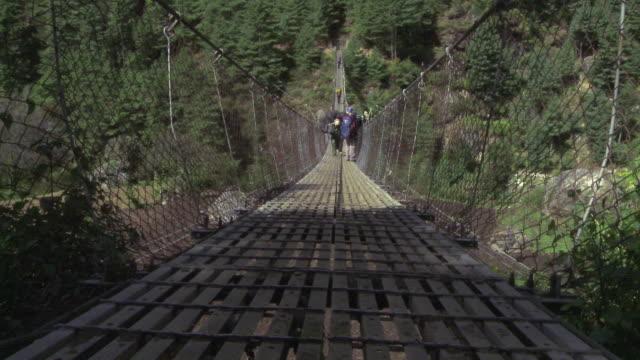 vídeos de stock e filmes b-roll de people carrying packs crossing a bridge in nepal. - ponte suspensa
