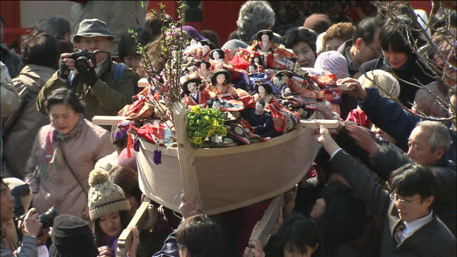 People carrying wooden boats filled with dolls on which wishes are written before being set adrift in sea as part of annual festival, Awashima Shrine, Wakayama