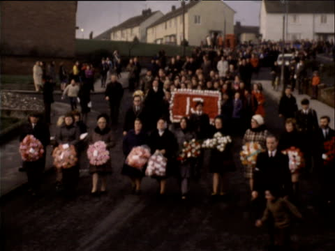 people carrying wreaths and banners march through londonderry to unveiling of memorial for bloody sunday victims 26 jan 74 - sonntag stock-videos und b-roll-filmmaterial