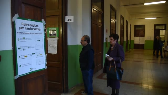 People cast tehir ballots for the Italy's two richest regions Lombardy and Veneto's autonomy referendum at a polling station in Milan Italy on...