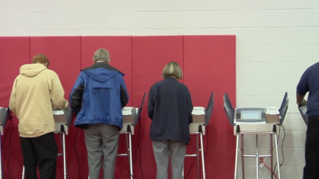 ms, pan, people casting their votes at electronic voting machines, toledo, ohio, usa - 投票点の映像素材/bロール