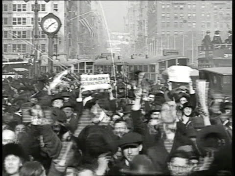 europe people celebrating in crowded street waving hands paper trolley cars parked bg effigy of kaiser wilhelm ii in air new york people celebrating... - 停戦点の映像素材/bロール