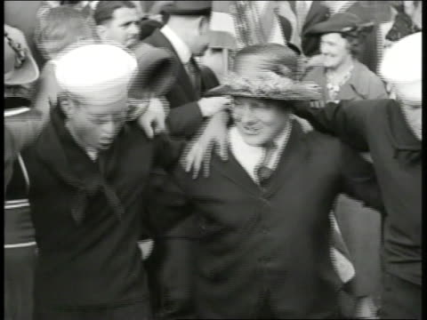People celebrating outside 'The Day' newspaper office sailors dancing w/ others riding in horse buggy MS Overweight sailor turning small noise maker...