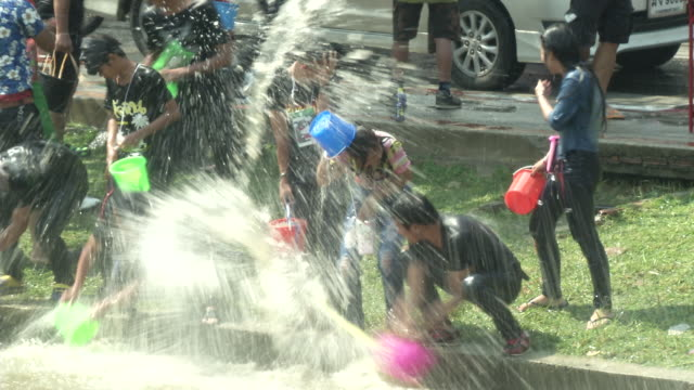 people celebrating thai new year or songkran around the moat and city walls of chiang mai, thailand. new year is traditionally celebrated by... - 水かけっこ点の映像素材/bロール