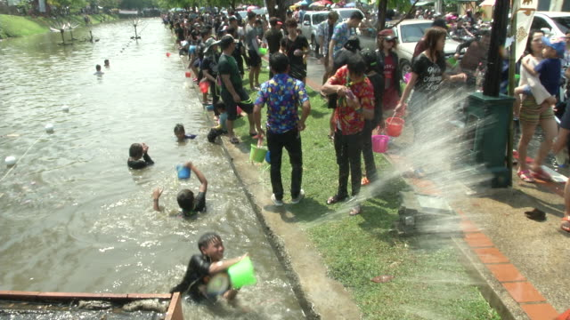 people celebrating thai new year or songkran around the moat and city walls of chiang mai, thailand. new year is traditionally celebrated by... - moat stock videos & royalty-free footage