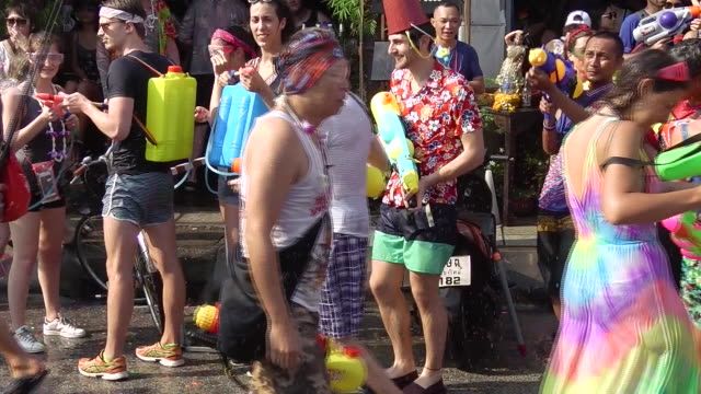 People celebrating Thai New Year or Songkran around the moat and city walls of Chiang Mai Thailand New Year is traditionally celebrated by splashing...