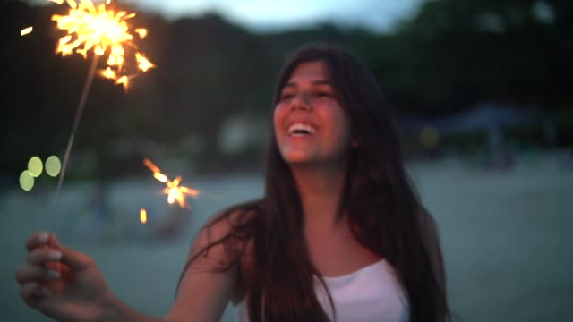 people celebrating the new year on the beach with sparkler - sparkler stock videos & royalty-free footage