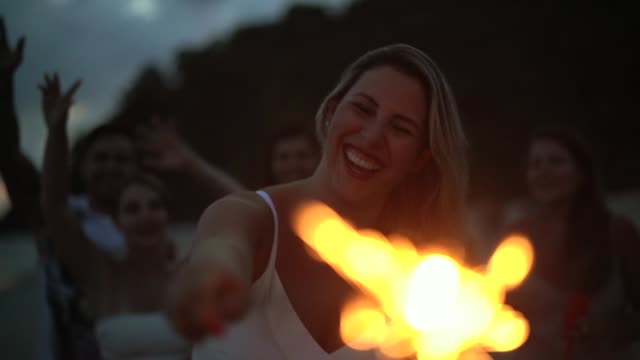 vídeos de stock e filmes b-roll de people celebrating the new year on the beach with sparkler - brazilian ethnicity