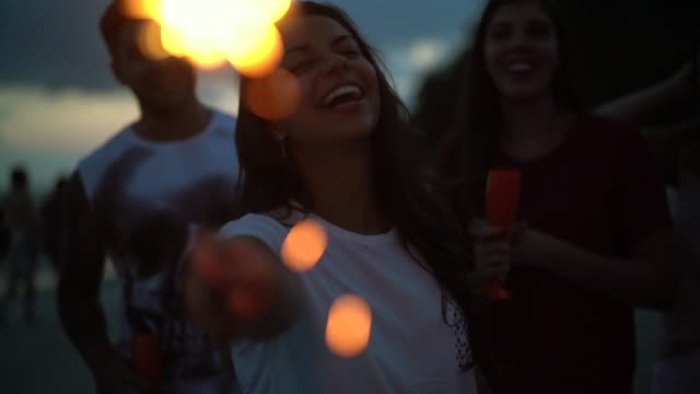 people celebrating the new year on the beach with sparkler - aspirations stock videos & royalty-free footage