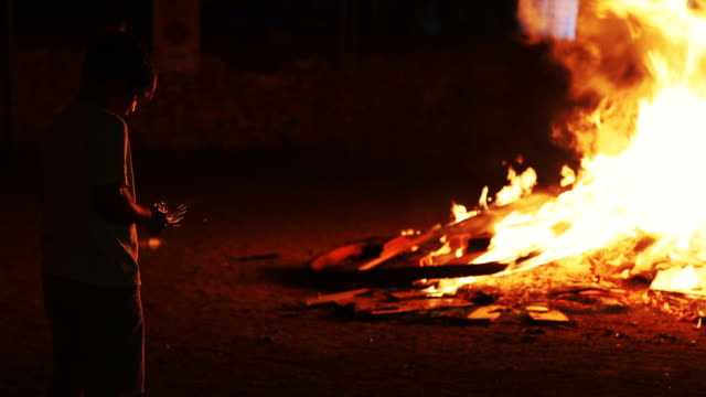 People celebrating the summer solstice in Catalonia at night with fireworks and bonfires in the city streets.