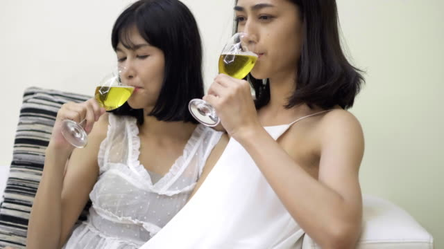People, celebration, homosexuality, same-sex marriage and love concept lesbian couple drinking wine.LGBT Celebrations & Milestones.LGBTQ Home Life