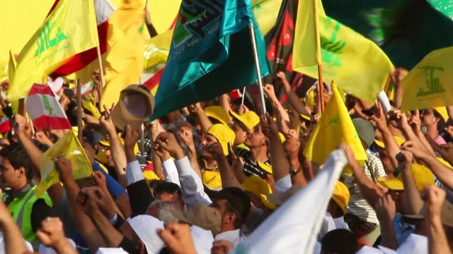people chanting at hezbollah rally crowd waves hezbollah and syrian flags wearing yellow caps - hezbollah stock videos & royalty-free footage