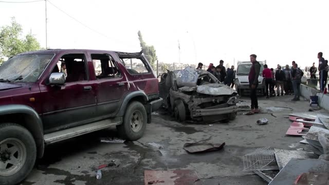 people check the site of a car bomb that exploded the previous day in mosul killing three people and wounding twelve medical and security officials... - iraq stock videos & royalty-free footage