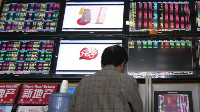 people checking chinese stock market in beijing china - economia video stock e b–roll