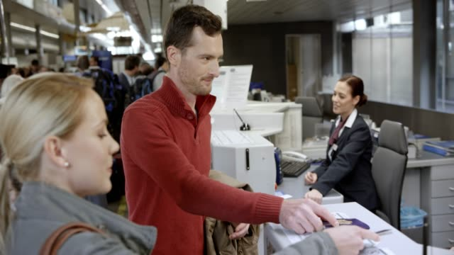 People checking in at the check in desk at the airport and handing over their luggage