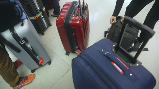 people checking their own luggages  at the airport - wheeled luggage stock videos and b-roll footage