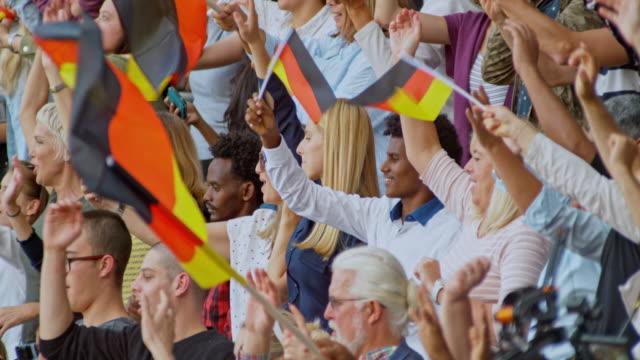 stockvideo's en b-roll-footage met slo mo people cheering and waving german flags on the stadium tribune - harmonie