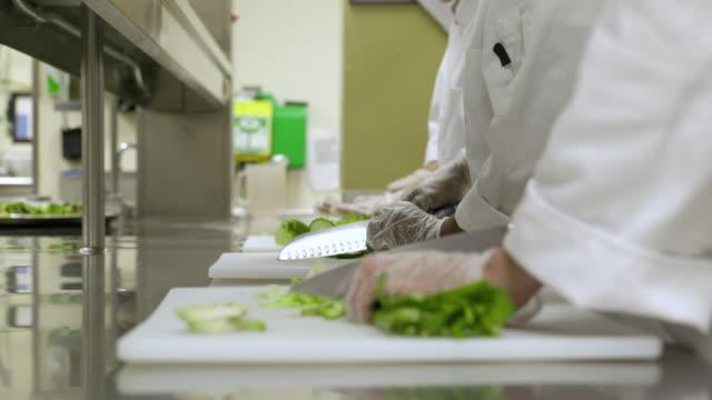 vídeos de stock e filmes b-roll de people chopping fresh celery in commercial kitchen, close up. - chefe de cozinha