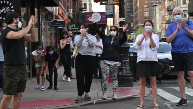 stockvideo's en b-roll-footage met people clap and cheer to show their appreciation for frontline health care workers at the nightly #clapbecausewecare during the coronavirus pandemic... - bewondering