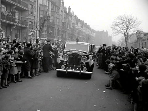 People clap and wave as the royal car carrying Queen Elizabeth and the Duke of Edinburgh arrives at the BBC's Maida Vale studios 1953