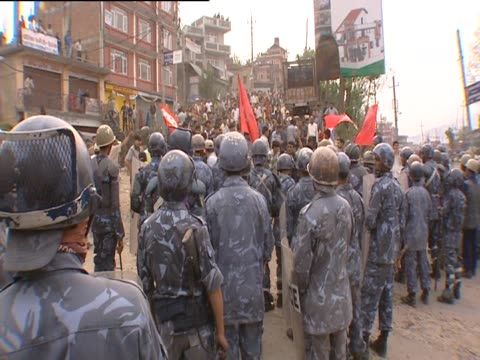 People clapping and chanting watched by police with riot shields at protest in Kathmandu