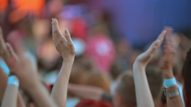People clapping hands at a concert in daylight