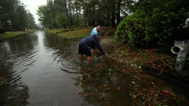 people clean debris away from the storm drains, after hurricane florence hit the area on september 14, 2018 in wilmington, north carolina. hurricane... - wilmington north carolina stock-videos und b-roll-filmmaterial