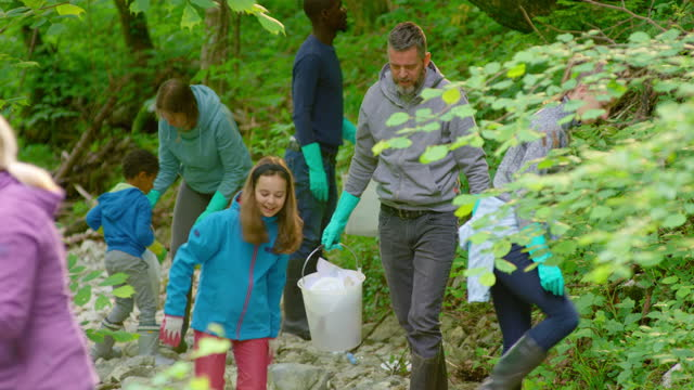people cleaning the forest and picking trash in the local cleanup action - picking up stock videos & royalty-free footage