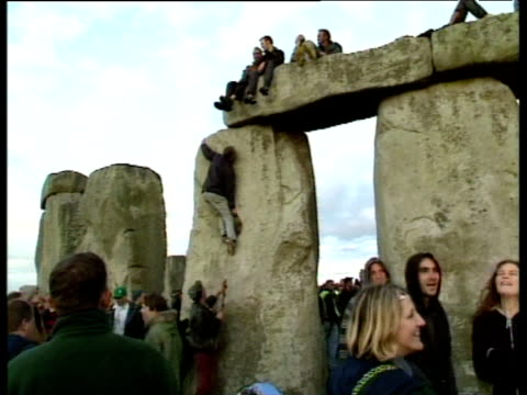 vídeos y material grabado en eventos de stock de people climb stonehenge during celebrations to mark last summer solstice of millennium wiltshire 21 jun 99 - escalada libre